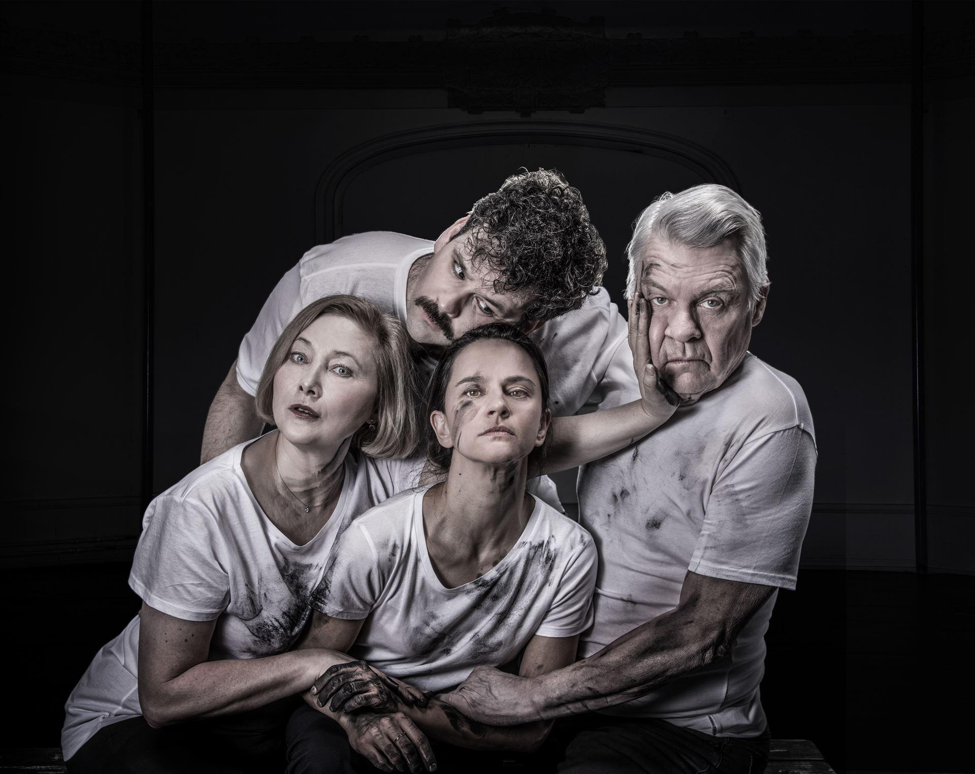 Gråtonad bild med fyra människor i smutsiga t-shirts. Foto: Dramaten